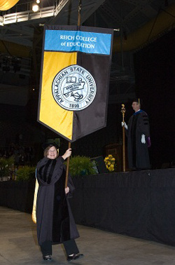 faculty member holding the reich college of education banner at graduation